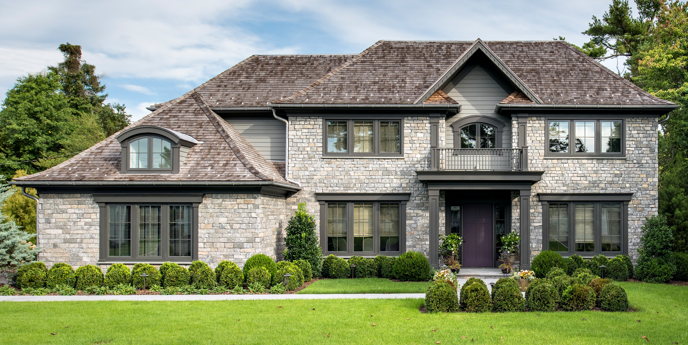 Exterior photo of a stone and cedar roof home